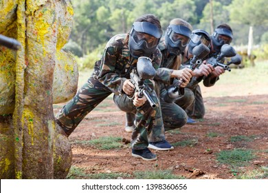 Portrait of team of cheerful  smiling adult people playing on paintball battlefield outdoor