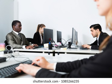 Portrait of team of diligent efficient positive   buisness people working with laptops in  office
