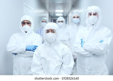 Portrait of team of doctors in protective uniforms and masks looking at camera while working during coronavirus pandemic