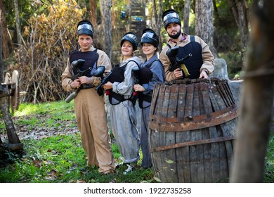 Portrait of team male and female paintball players with marker guns ready for game outdoors