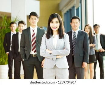 portrait of a team of successful asian businessmen and businesswomen, looking at camera smiling.