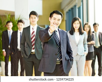 portrait of a team of successful asian businessmen and businesswomen, pointing and looking at camera smiling.