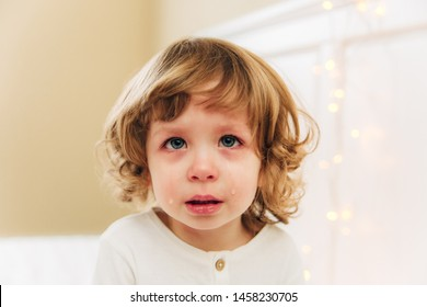 Portrait of tearful little girl.Small cute girl is crying.indoor.curly hair and blue eyes.