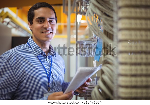 Portrait of technician analyzing server in server room