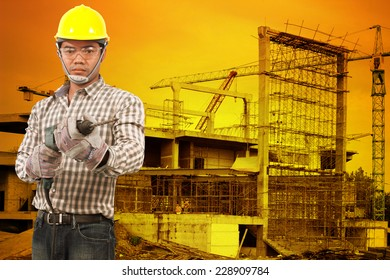 Portrait of technician in protective safety equipment goggles hard hat with drill  against building construction crane with beautiful sunset