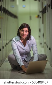 Portrait of technician siting on floor and using laptop in server room