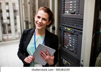 Portrait of technician using digital tablet in server room