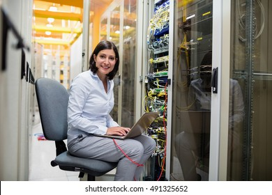 Portrait of technician working on laptop in server room