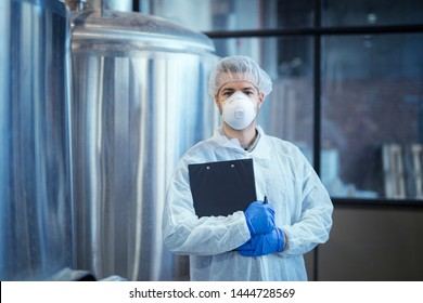 Portrait of technologist in white uniform with hairnet and protective mask and gloves standing in pharmaceutical or food factory with arms crossed.