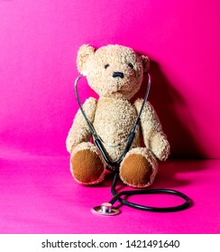 Portrait of a teddy bear with stethoscope for checking health over pink background for playing doctor concept