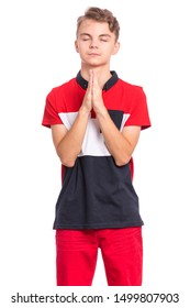 Portrait of teen boy praying, isolated on white background. Cute caucasian teenager with hands folded in prayer hoping for better. Child asking God for good luck, success or forgiveness.