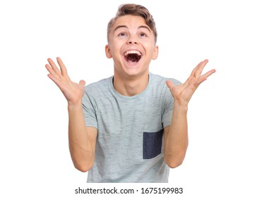 Portrait of teen boy raised hands and trying to catch something. Cute caucasian young teenager smiling and looking up, isolated on white background. Joyful child having fun.
