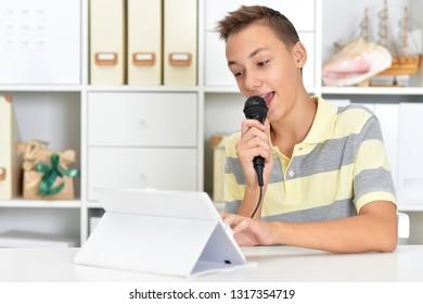 Portrait of a teen boy singing karaoke