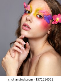 Portrait of teen girl with hand near face. Young female with unusual stylish make-up and false fashion feather eyelashes. Orchid flower in wavy hair.
