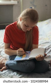 Portrait of a teen girl at home - drawing the picture