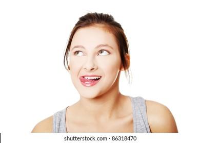 Portrait of teen girl licking her lips and looking on upper left corner.