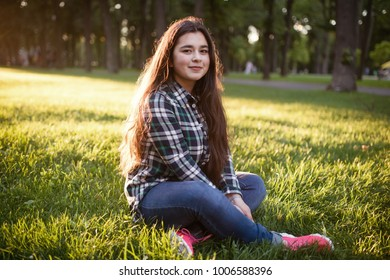 Portrait of the teen girl on lawn in summer day.