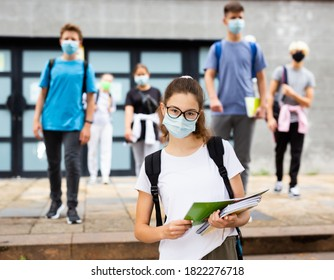 Portrait of teen girl student in face mask on her way to college in warm autumn day. Forced precautions in COVID pandemic.