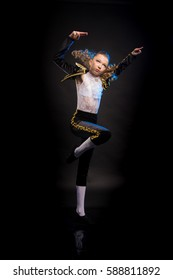 Portrait of teen girl in a suit of black bullfighter jumping, dancing and posing on a dark background in the studio