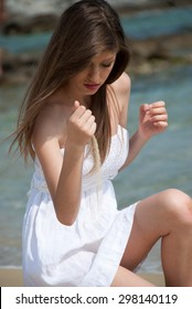 Portrait of a teen girl with white dress kneeling at the beach and play with the sand. Sea and land as background