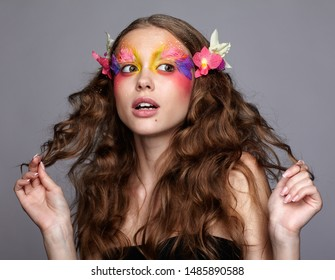 Portrait of teen girl. Young female with unusual stylish make-up and false fashion feather eyelashes. Orchid flower in wavy hair.