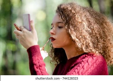 Portrait of teen girlr uses lipstick outside