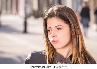 portrait of a teen sad girl closeup, outdoor city street