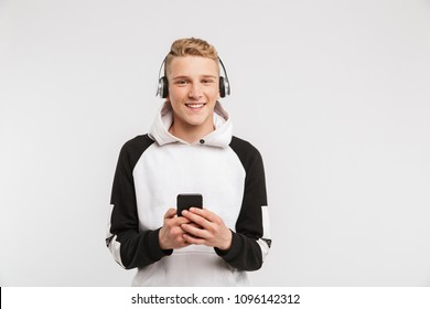 Portrait of teenage boy 16-18 years old wearing hoodie smiling and listening to music on smartphone via wireless headphones isolated over white background