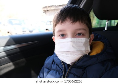 A portrait of teenage boy in a car wearing white surgical medical face mask as a protection against virus disease, coronavirus protection and prevention concept, covid-19.