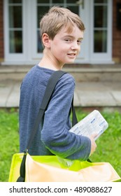 Portrait Of Teenage Boy Delivering Newspaper To House