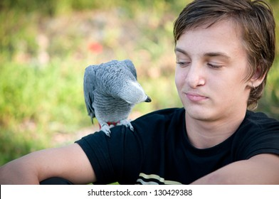 Portrait of a teenage boy with a gray parrot Jaco.