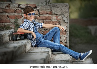 Portrait of a teenage boy with a skateboard on the steps of the stairs in the park on a summer afternoon.