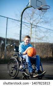 Portrait Of Teenage Boy In Wheelchair Playing Basketball On Outdoor Court