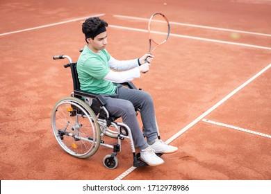 A portrait of teenage boy in wheelchair playing tennis