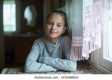Portrait of a teenage cute girl sitting at the table.