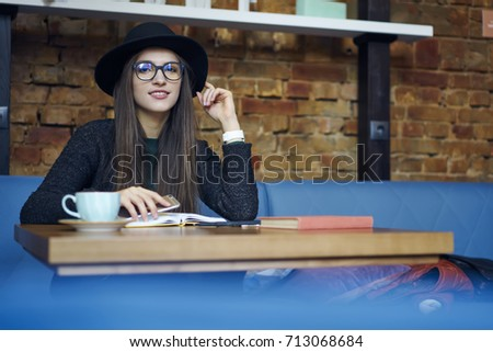 f55a142be9f4 Portrait of teenage female hipster girl in trendy eyewear and hat sitting  in cafe resting,