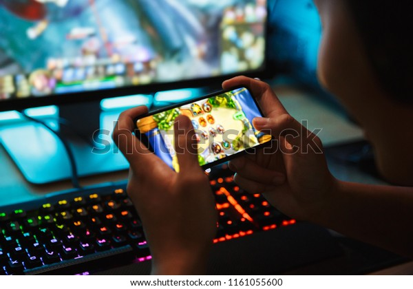 Portrait of teenage gamer boy playing video games on smartphone and computer in dark room wearing headphones and using backlit colorful keyboard