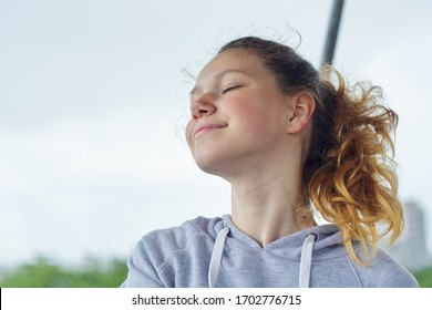 Portrait of teenage girl 15 years old, dreaming girl with closed eyes, smiling pretty female in gray sweatshirt, background sky
