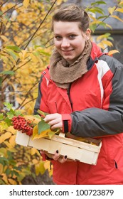 Portrait of teenage girl with basket of autumn leaves and berries
