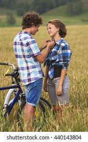 Portrait of a teenage girl and boy on a bicycle in a summer field of rye