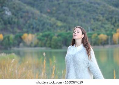Retrato de una adolescente respirando aire fresco en un lago en invierno