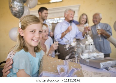 Portrait of teenage girl holding gift with family celebrating in the background