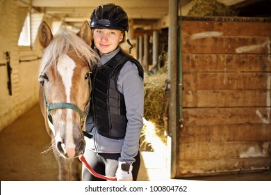 Portrait of teenage girl with horse in stable