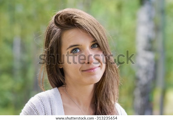 Portrait of a teenage girl with long hair and bright eyes on a background of green forest
