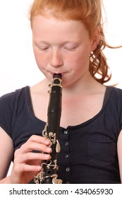 Portrait of a teenage girl playing clarinet on white background