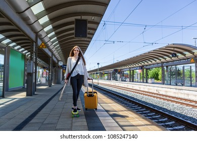 portrait of a teenage girl with a quitar and skateboard on the railway station