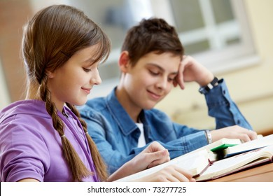 Portrait of teenage girl reading book with her classmate at background