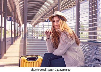 portrait of a teenage girl with a suitcase on the railway station