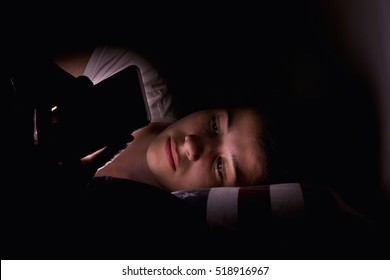 Portrait of a teenage girl using mobile phone on dark bed
