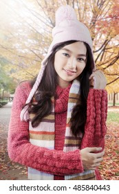 Portrait of teenage girl wearing warm clothes and hat, looking and smiling at the camera, autumn in the park.